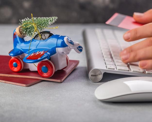 Kleines flugzeug mit weihnachtsbaum, pässen, tastatur, kreditkarte auf grauer frauenhand schreibt
