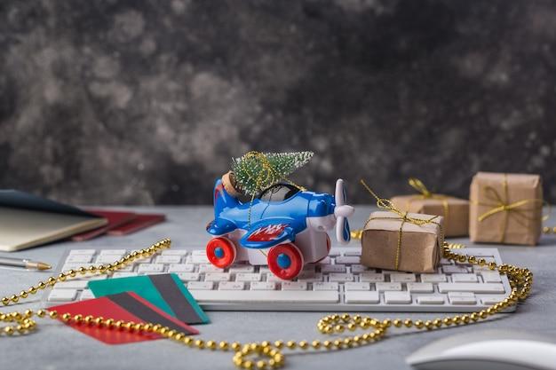 Kleines flugzeug mit weihnachtsbaum, pässen, tastatur, kreditkartenferien