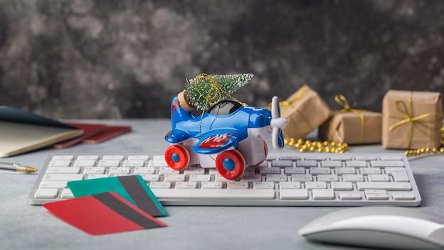 Kleines flugzeug mit weihnachtsbaum, pässen, tastatur, kreditkartenurlaub, tourismus, reise für die online-buchung von tickets für heiligabend