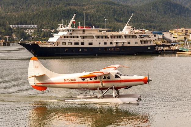 Kleines flugzeug und kreuzfahrtschiff in alaska