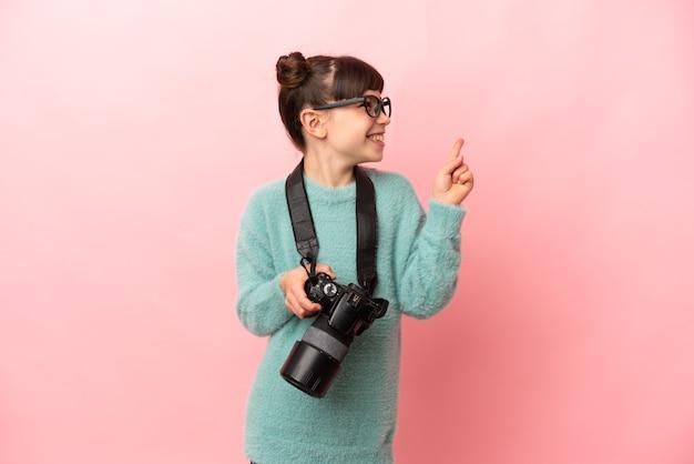 Kleines fotografenmädchen, das isoliert auf eine großartige idee zeigt