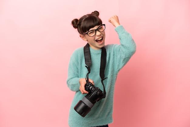 Kleines fotografmädchen lokalisiert auf rosa, das einen sieg feiert