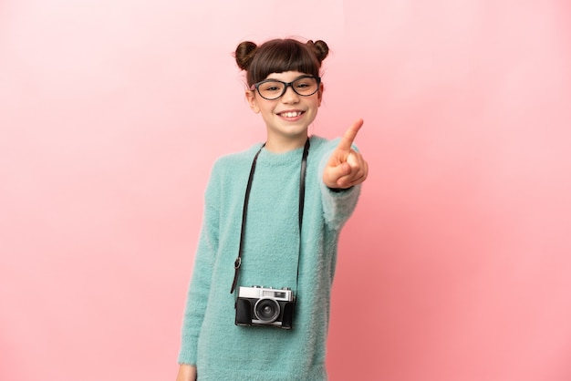 Kleines fotografmädchen lokalisiert auf rosa wand, die einen finger zeigt und hebt