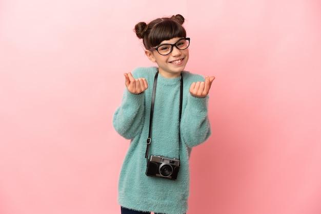 Kleines fotografmädchen lokalisiert auf rosa wand, die geldgeste macht