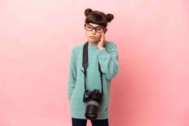 Kleines fotografmädchen lokalisiert auf rosa wand mit kopfschmerzen