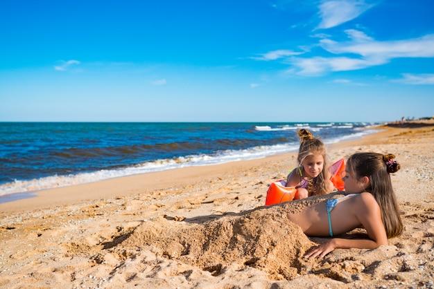 Kleines fröhliches mädchen begraben ihre ältere schwester im sand, während sie am strand spielen