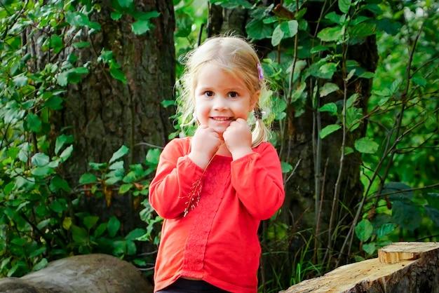 Kleines fröhliches mädchen sitzt auf einem baumstamm im wald.
