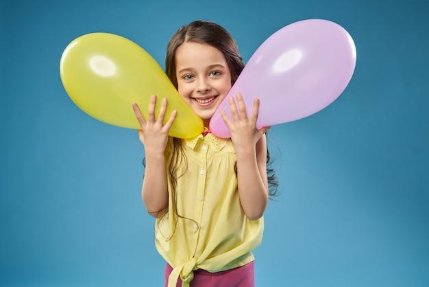Kleines fröhliches modell, das mit luftballons aufwirft.