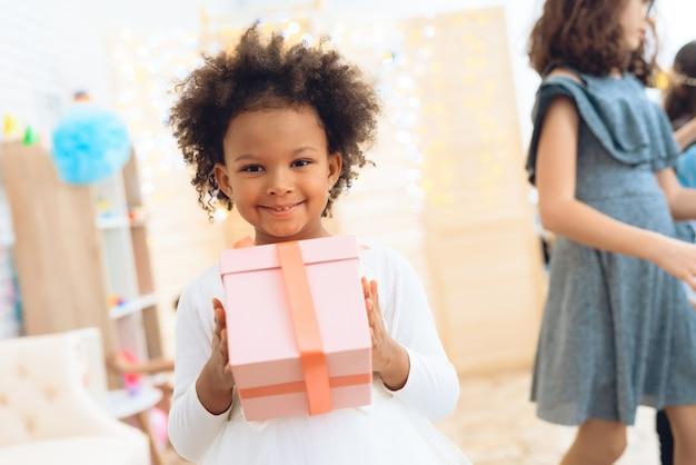 Kleines frohes mädchen hält geschenk im rosa kasten an der geburtstagsfeier