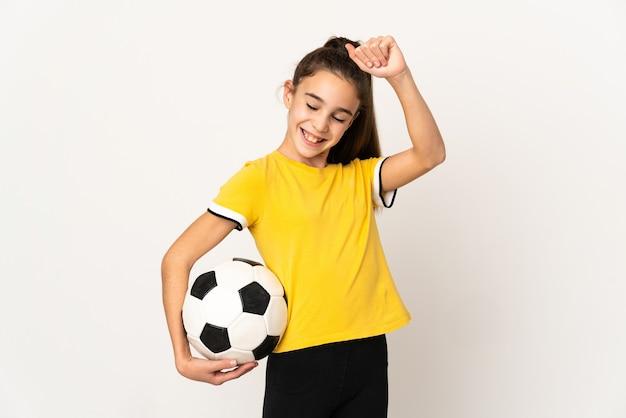 Kleines fußballspielermädchen lokalisiert auf weißem hintergrund, der einen sieg feiert