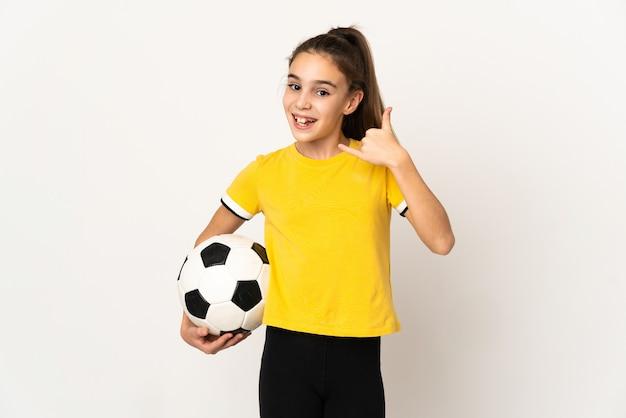 Kleines fußballspielermädchen lokalisiert auf weißem hintergrund, der telefongeste macht. ruf mich zurück zeichen