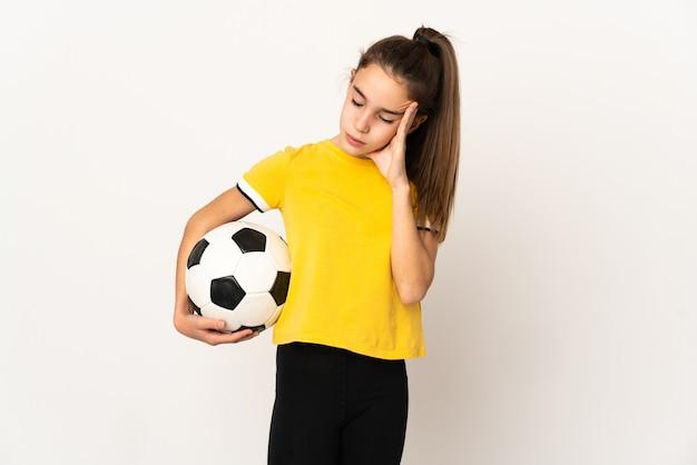 Kleines fußballspielermädchen lokalisiert auf weißem hintergrund mit kopfschmerzen