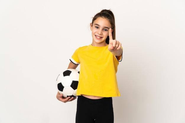Kleines fußballspielermädchen lokalisiert auf weißer wand, die einen finger zeigt und hebt