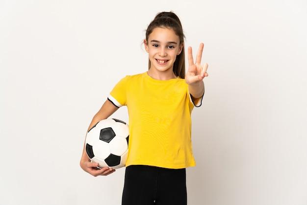 Kleines fußballspielermädchen lokalisiert auf weißer wand, die lächelt und siegeszeichen zeigt