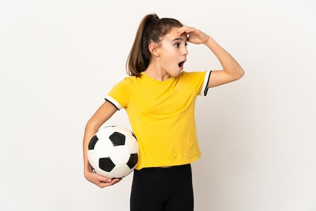 Kleines fußballspielermädchen lokalisiert auf weißer wand, die überraschungsgeste tut, während sie zur seite schaut