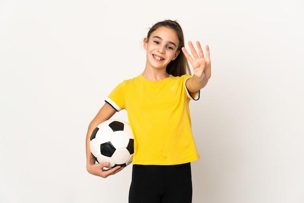 Kleines fußballspielermädchen lokalisiert auf weißer wand glücklich und zählt vier mit den fingern
