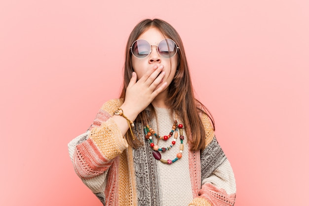 Kleines gähnendes hippiemädchen, das eine müde geste bedeckt mund mit seiner hand zeigt.