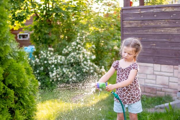 Kleines gärtnermädchen, sie gießt blumen auf dem rasen in der nähe der hütte