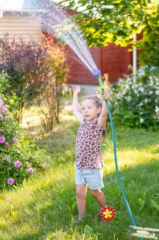 Kleines gärtnermädchen, sie gießt blumen auf dem rasen