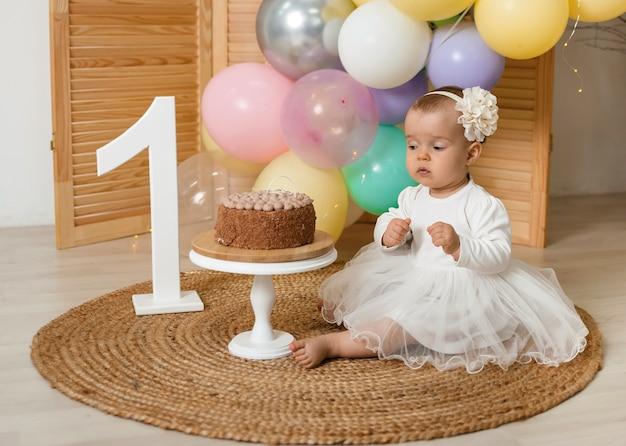 Kleines geburtstagskind in einem weißen festlichen kleid sitzt und schaut auf einen kuchen mit sahne