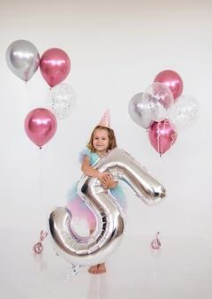 Kleines geburtstagskind steht mit luftballons und einer foliennummer fünf auf weißem hintergrund. kindergeburtstag