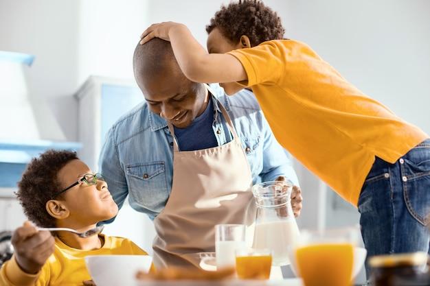 Kleines geheimnis. angenehmer kleiner junge, der seinem vater etwas ins ohr flüstert, während der mann beim frühstück milch in die gläser seiner söhne gießt