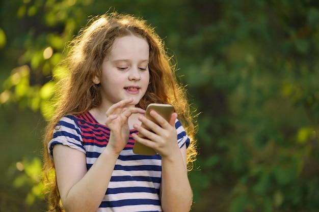 Kleines gelocktes mädchen, das draußen smartphone verwendet.