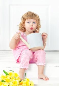 Kleines gelocktes mädchen im rosa kleid und barfuß sitzt auf einem weißen portal und spielt mit gießkanne.