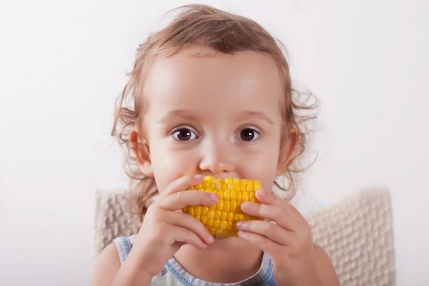Kleines gelocktes nettes mädchen, das den mais sitzt auf dem stuhl isst.