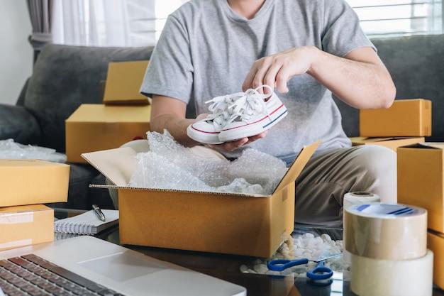 Kleines geschäftspaket für versand an kunden, freiberuflicher mann des jungen unternehmers kmu, der mit verpackungsschuh in kastenlieferungs-onlinemarkt auf bestellung arbeitet und zu hause paketprodukt vorbereitet