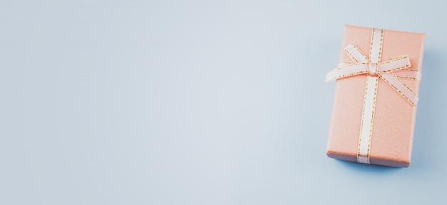 Kleines geschenk auf einem pastellhintergrund, nahaufnahme. geschenkbox mit schleife
