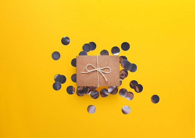 Kleines geschenk eingewickelt im kraftpapier auf einem gelben hintergrund mit silbernen konfettis.