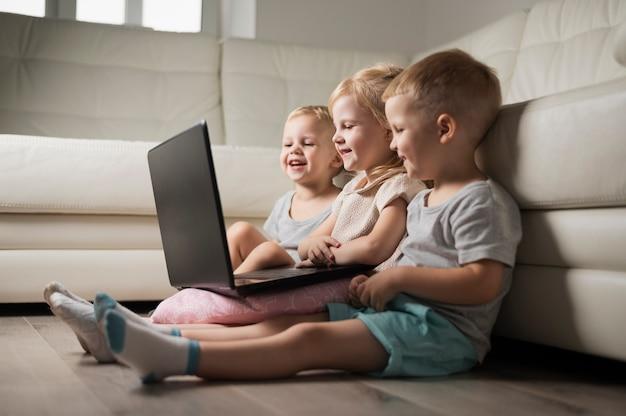 Kleines geschwistersitzen auf boden und betrachten des laptops