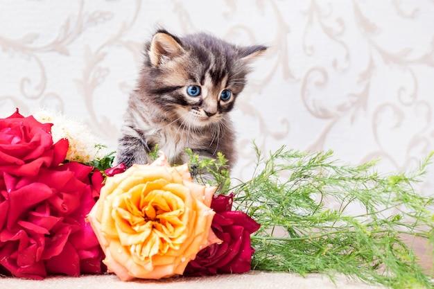 Kleines gestreiftes kätzchen mit einem blumenstrauß. herzlichen glückwunsch zu ihrem geburtstag oder anderen feiertagen