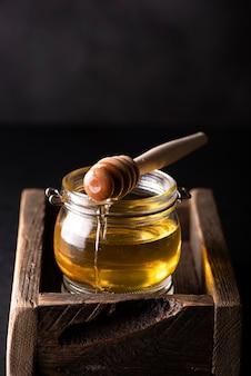 Kleines glas honig in einer holzkiste
