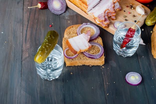 Kleines glas mit russischem wodka, sandwich mit geräuchertem speck und salzgurke