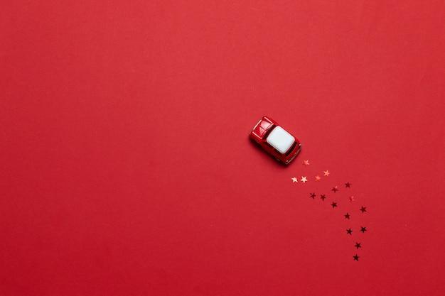 Kleines glattes spielzeugauto mit goldenem stern funkelt auf einem roten hintergrund. feiertagsgrußkarte oder -fahne.