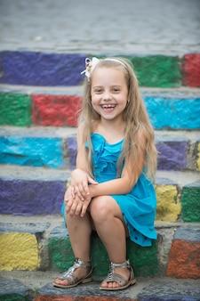 Kleines glückliches baby oder süßes kind mit entzückendem lächelndem gesicht und schleife im blonden haar im blauen kleid im freien, das auf buntem steinigem treppenhintergrund sitzt