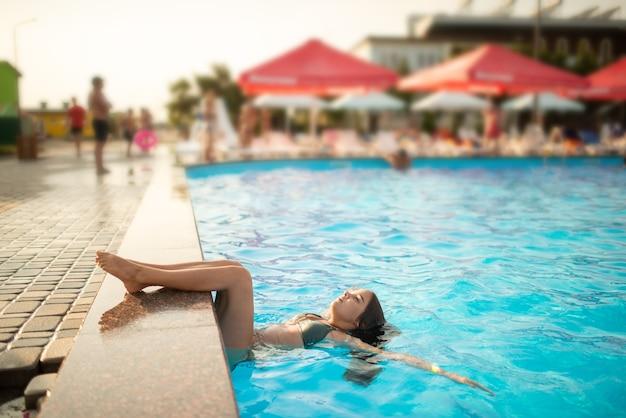 Kleines glückliches junges mädchen schwimmt im pool und genießt warmes wasser, während es ihre füße vom rand des pools hält