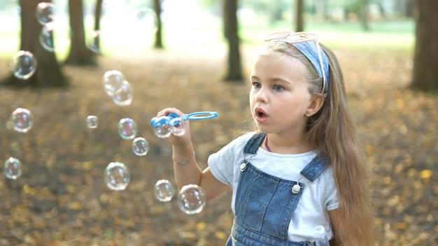 Kleines glückliches kindermädchen, das draußen im sommerpark seifenblasen bläst.