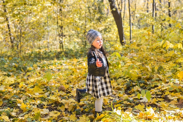 Kleines glückliches kindermädchen, das im herbstpark geht
