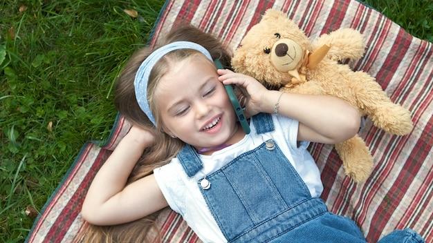 Kleines glückliches kindermädchen, das mit ihrem teddybären auf dem grünen rasen liegt und am handy spricht.