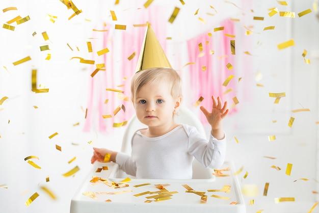 Kleines glückliches kleinkindbaby, das den ersten geburtstag feiert, der mit goldenem partyhut sitzt. fliegendes festliches konfetti