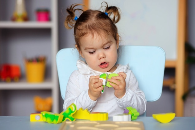 Kleines glückliches kleinkindmädchen, das am tisch spielt