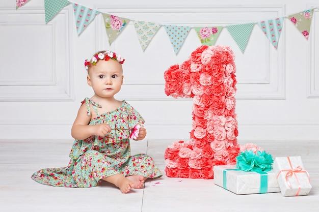Kleines glückliches kleinkindmädchen, das ersten geburtstag feiert.