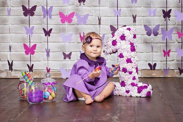 Kleines glückliches kleinkindmädchen, das ersten geburtstag feiert