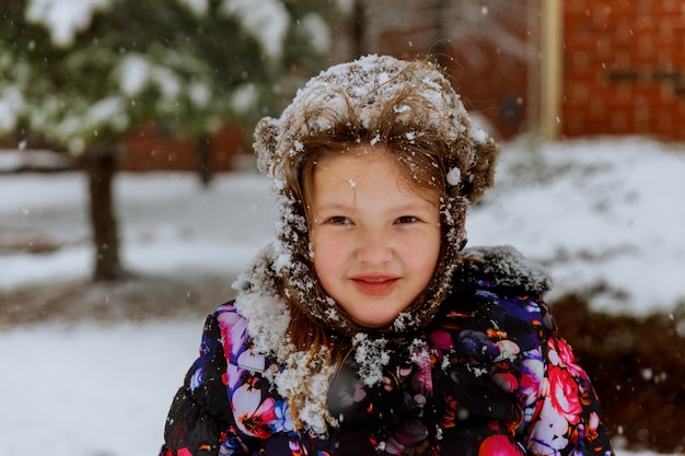 Kleines glückliches mädchen, das am schneebedeckten winter im freien spielt
