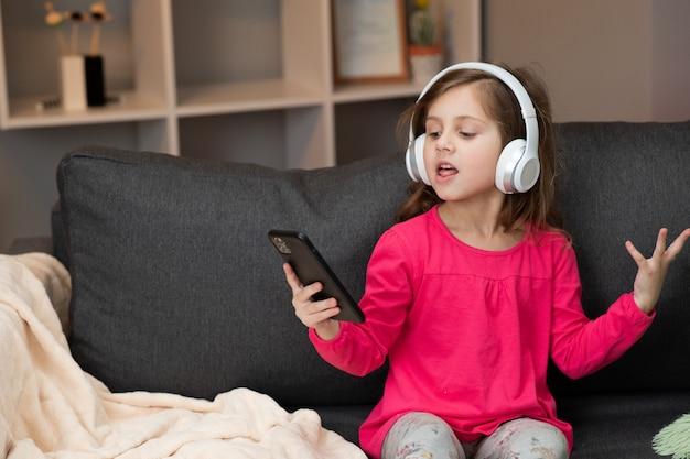 Kleines glückliches mädchen, das auf sofa tanzt, während musik zu hause in kopfhörern hört. mädchen, das kopfhörer tanzt, singt und sich zum rhythmus bewegt