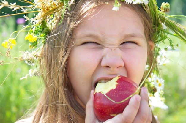 Kleines glückliches mädchen, das einen großen roten apfel an einem sommertag isst