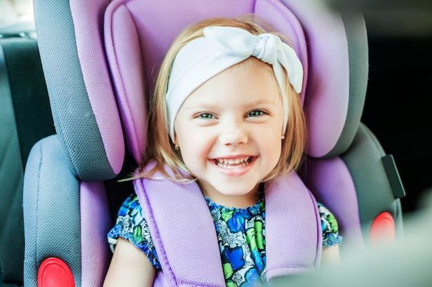 Kleines glückliches mädchen, das in einem babyautositz befestigt sitzt